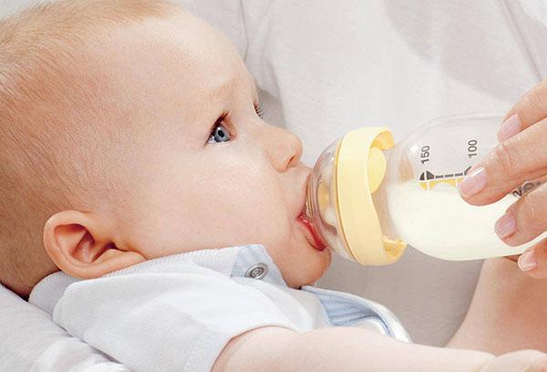 Ребенок пьет молоко из бутылочки