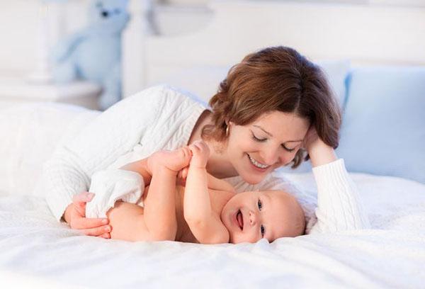 Веселый младенец с мамой на кровати