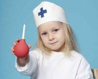 Девочка в костюме врача со спринцовкой