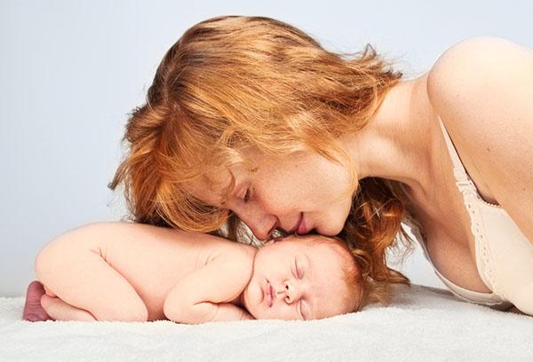 Женщина целует спящего младенца