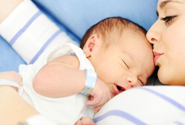 Мама целует спящего младенца