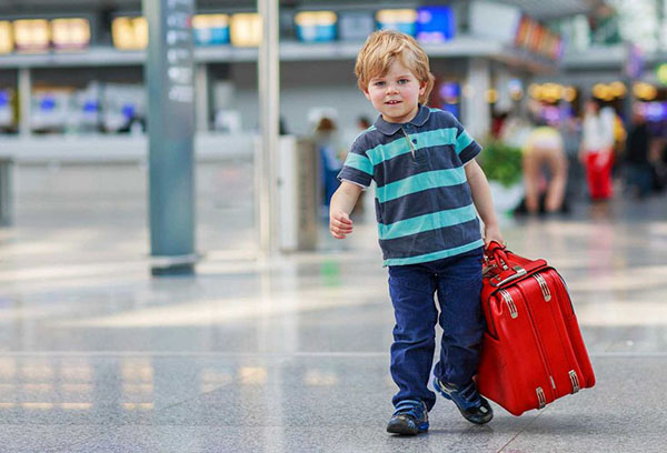 Ребенок с чемоданом в аэропорту