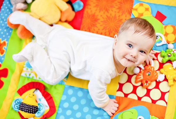 Пятимесячный ребенок на игровом коврике