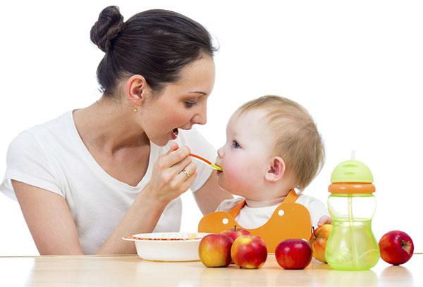 Мама кормит малыша яблочным пюре