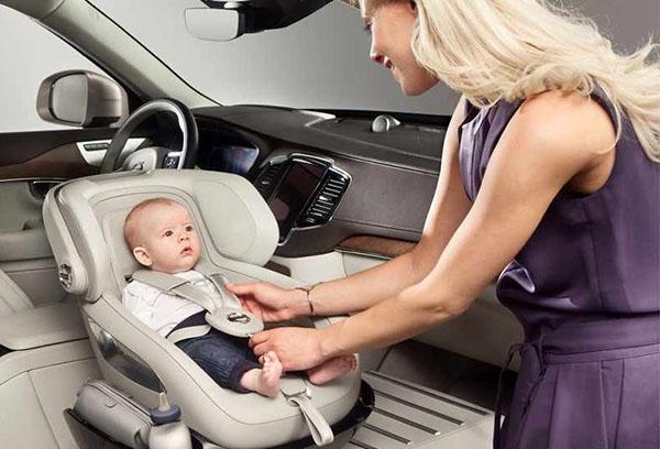 Мама усаживает малыша в автокресло