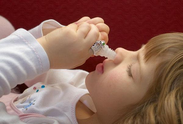 Девочка закапывает капли в нос