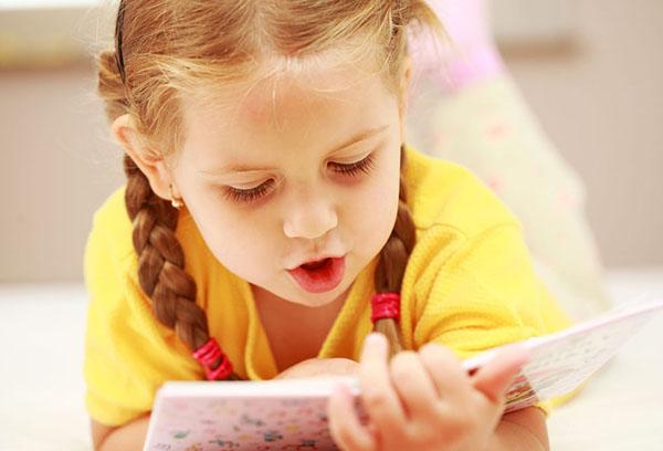 Девочка читает книгу вслух