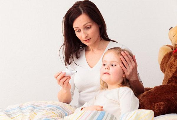 Мама измеряет температуру дочке